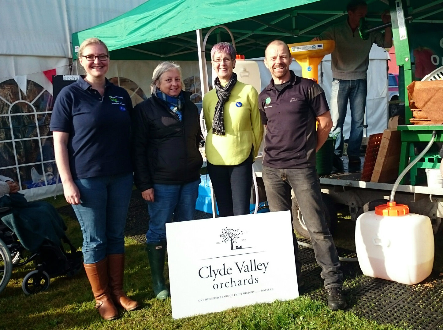 Donna Marshall (CAVLP Manager), Cheryl Osbourne (Clyde Valley Orchard Co-operative Ltd. Chair), Alison Cutforth (Heritage Lottery Fund Scotland) and Duncan Arthur (Clyde Valley Orchard Co-operative Ltd.) stand in front of the apple pressing demonstration at Fruit Day, Overton Farm