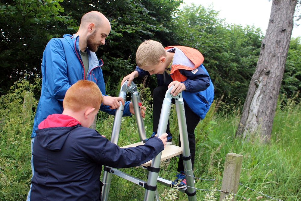 Pupils from Newfield Primary School enjoy use of the backpack ladder with Project Officer Michael