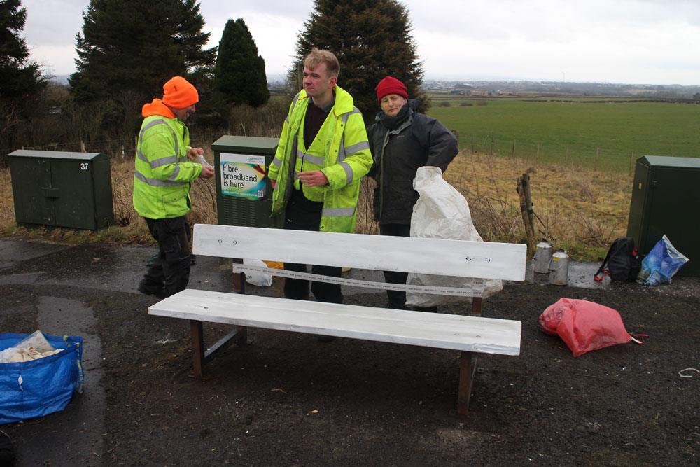 Clydesdale Community Initiatives volunteers complete an undercoat of paint on the public bench in Quarter